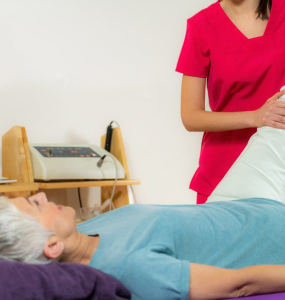 Physical Therapist Working with Leg. Senior Woman